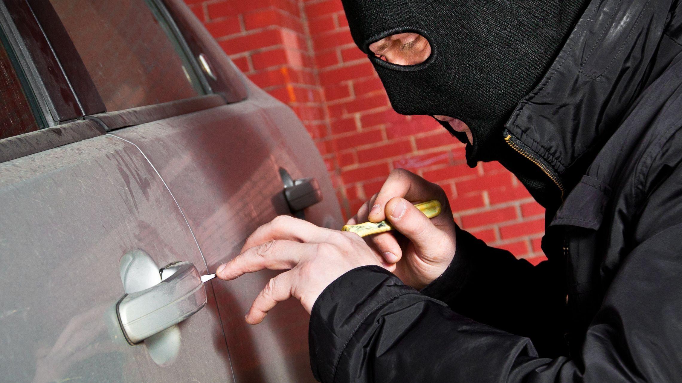 Symbolbild: Ein vermummter Mann bricht eine Autotür auf.