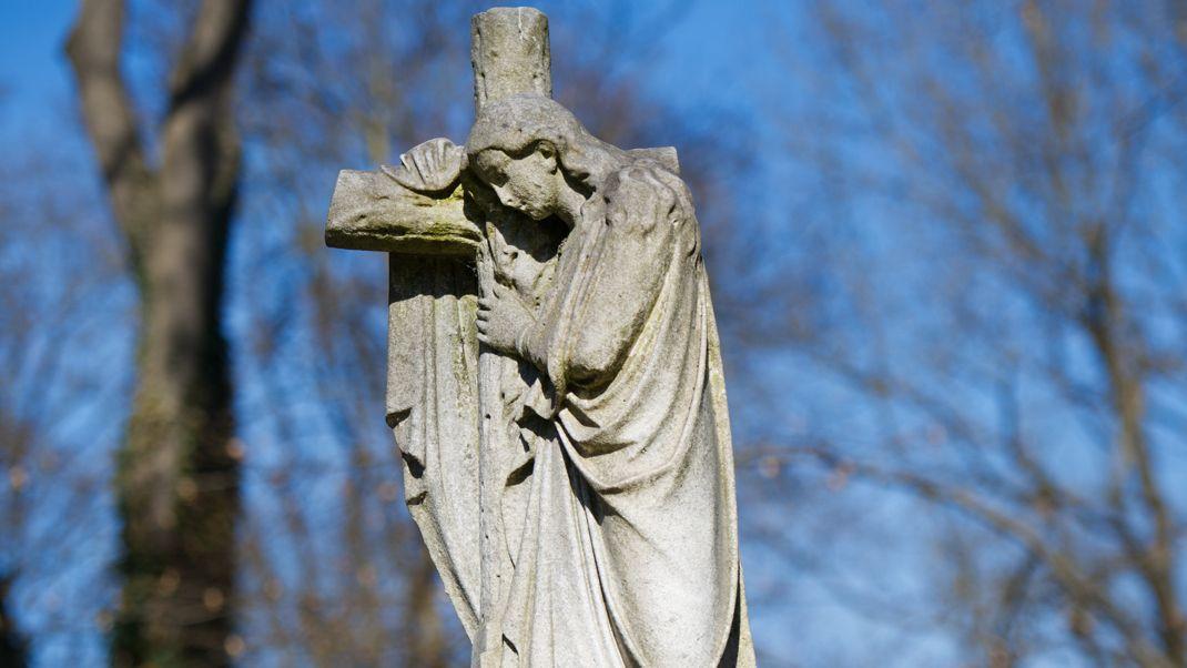 Eine Steinskulptur von einem Engel an einem Kreuz auf dem Alten Südfriedhof.