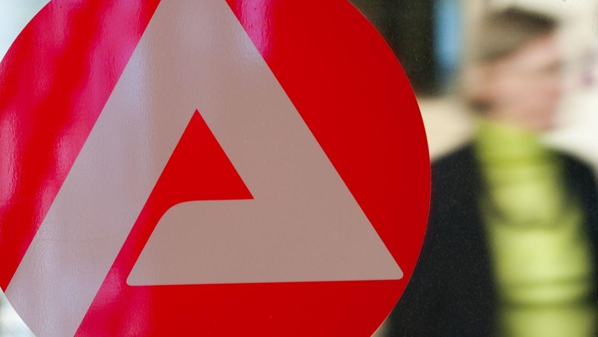 Eine Frau geht in der Bundesagentur für Arbeit an einem Logo der Arbeitsagentur vorbei.