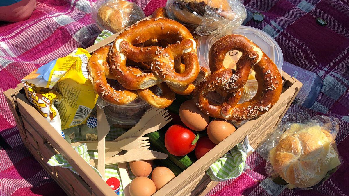 Auf einer Picknickdecke steht ein Brotzeitkorb aus Holz, darin unter anderem Brezen, Eier, Tomaten, Gurken und hölzernes Besteck.