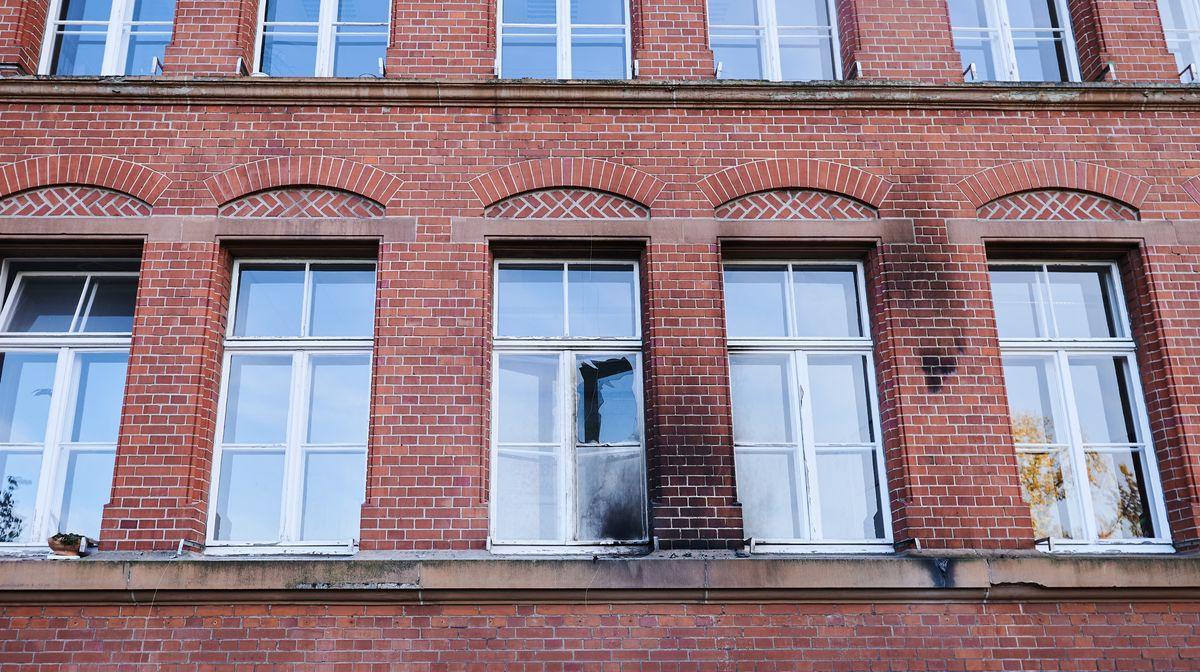 Fassade des Robert -Koch-Institutes mit Brandflecken und zerborstener Fensterscheibe.