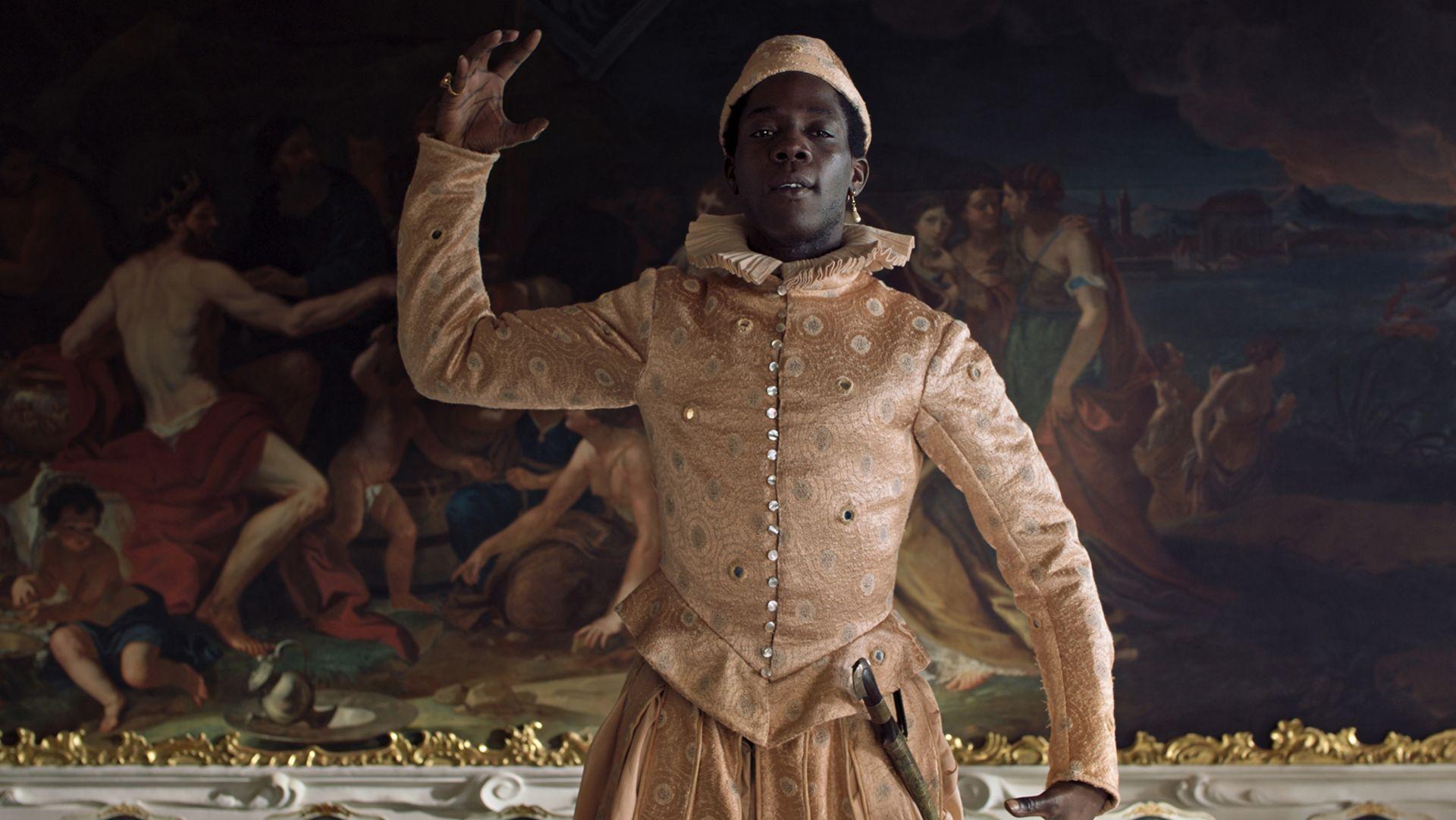 """Ein Mann in einem glänzenden Kostüm steht vor einem opulenten Gemälde: Szene aus """"Angelo"""""""