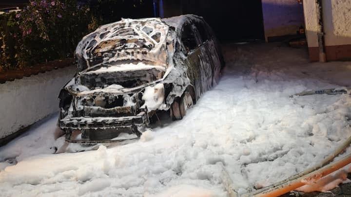 Löschschaum wurde überall vor der brennenden Garage und dem ausgebrannten Auto ausgebracht, um die Flammen zu löschen