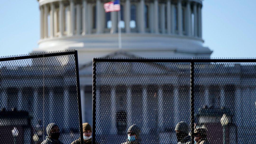 Beamte stehen hinter dem neuen Sicherheitszaun, der rund um das Kapitol errichtet wurde, nachdem am Tag zuvor Anhänger des scheidenden US-Präsidenten Trump gewaltsam das Parlamentsgebäude gestürmt hatten