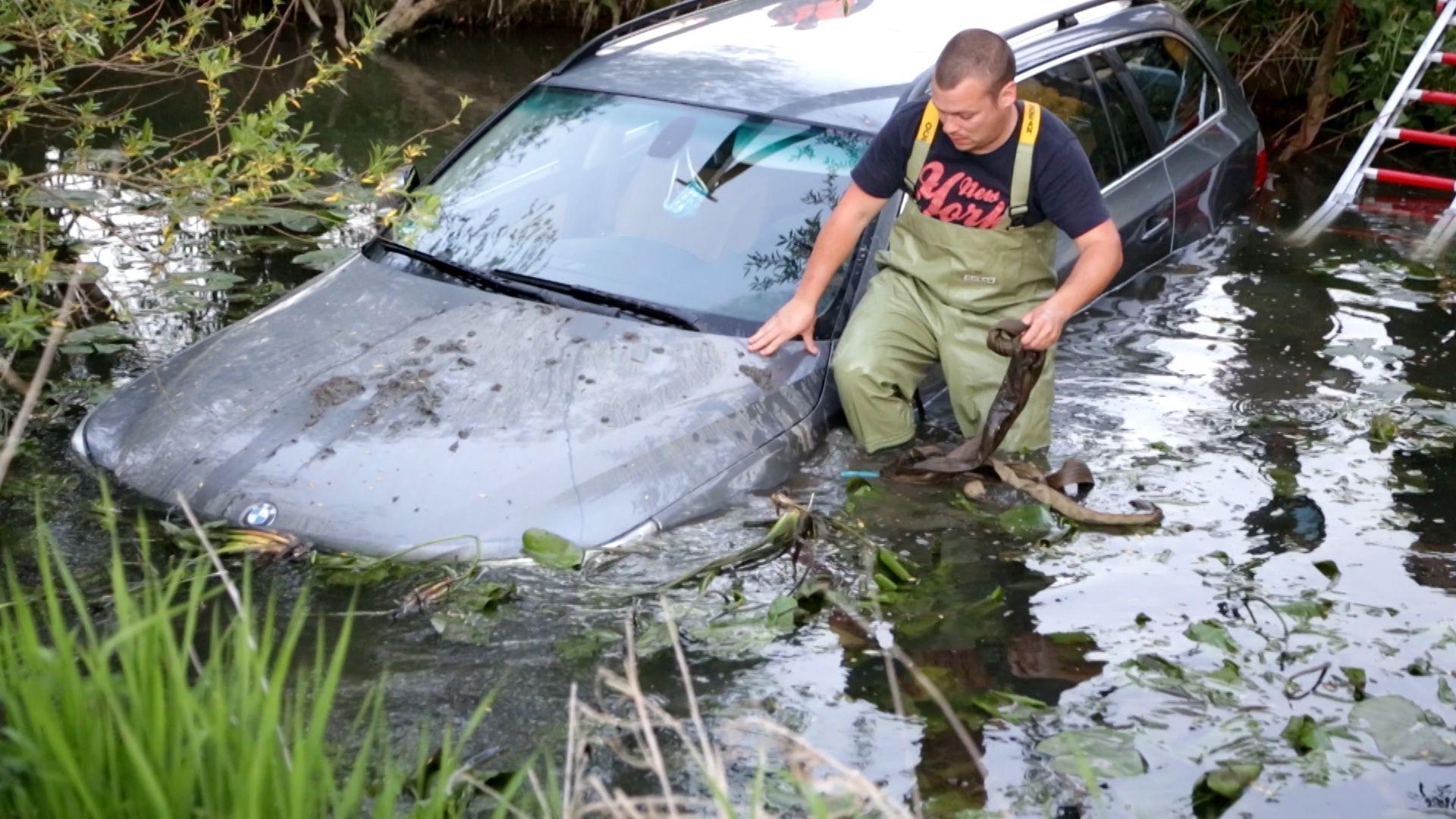 Ein Retter steht im Fluss, neben dem versenkten Auto