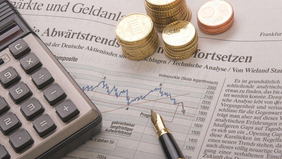 Ein Taschenrechner, ein Füller und Kleingeld liegen auf der Finanzseite einer Tageszeitung.