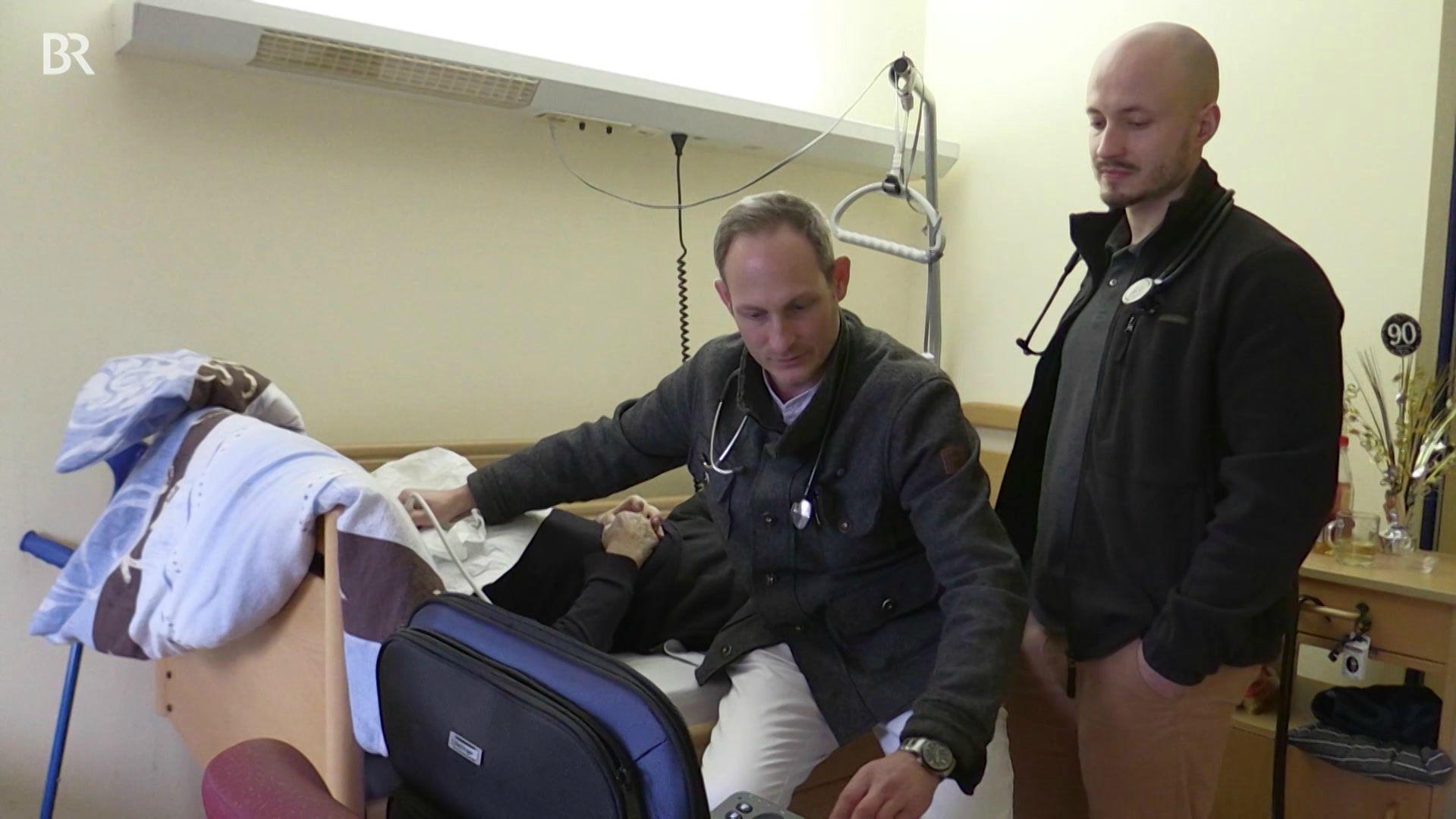 Hausarzt Dr. Sitter und Medizinstudent Stefan von Rotenhan am Bett eines Patienten