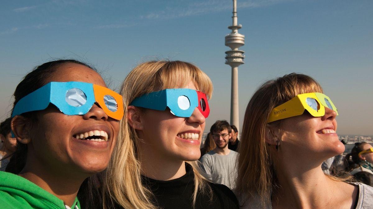 Drei junge Frauen mit Sonnenfinsternis-Schutzbrillen. Blicken Sie niemals ungeschützt ins Sonnenlicht!