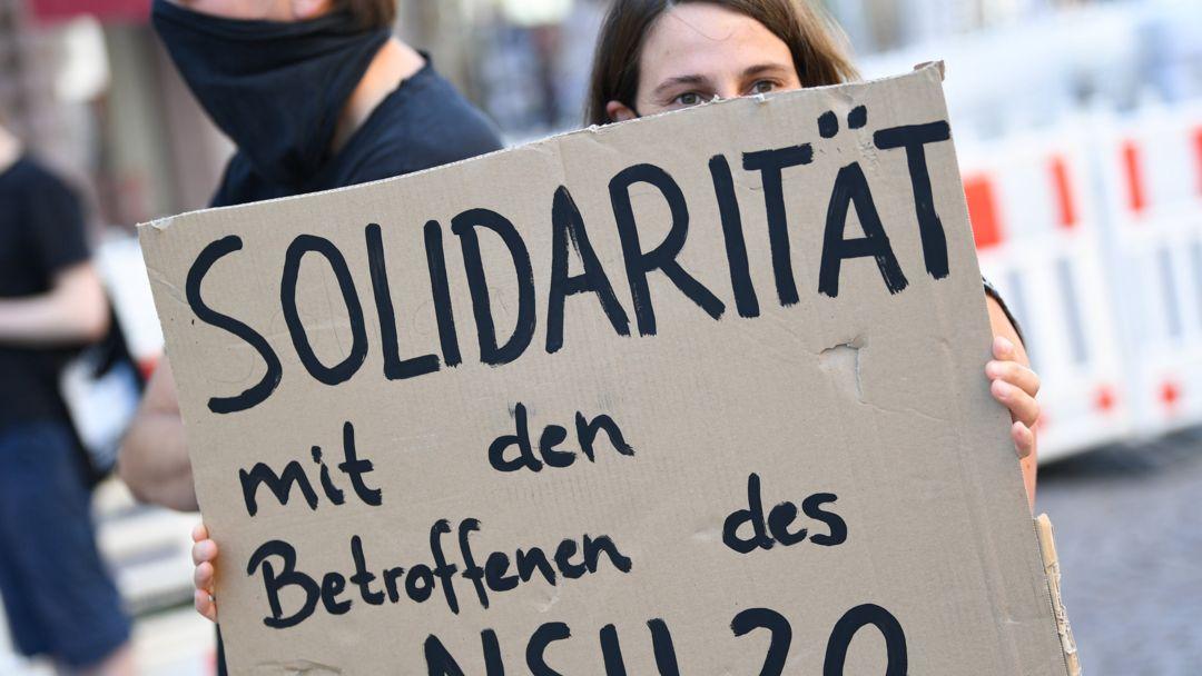 """Ein Demonstrantin hält während einer Kundgebung in der Wiesbadener Innenstadt ein Plakat mit der Aufschrift """"Solidarität mit den Betroffenen des NSU 2.0""""."""