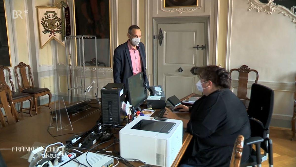 Ein Mann mit Mund-Nasen-Schutz steht vor einem Schreibtisch, an dem eine Frau sitz, die Passanträge bearbeitet.Langes Warten auf Dokumente in Coburg