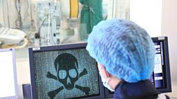 Arzt schaut während Herz-OP auf einen Monitor, auf dem ein Totenkopf einen Hackerangriff symbolisiert | Bild:Colourbox, Montage: BR