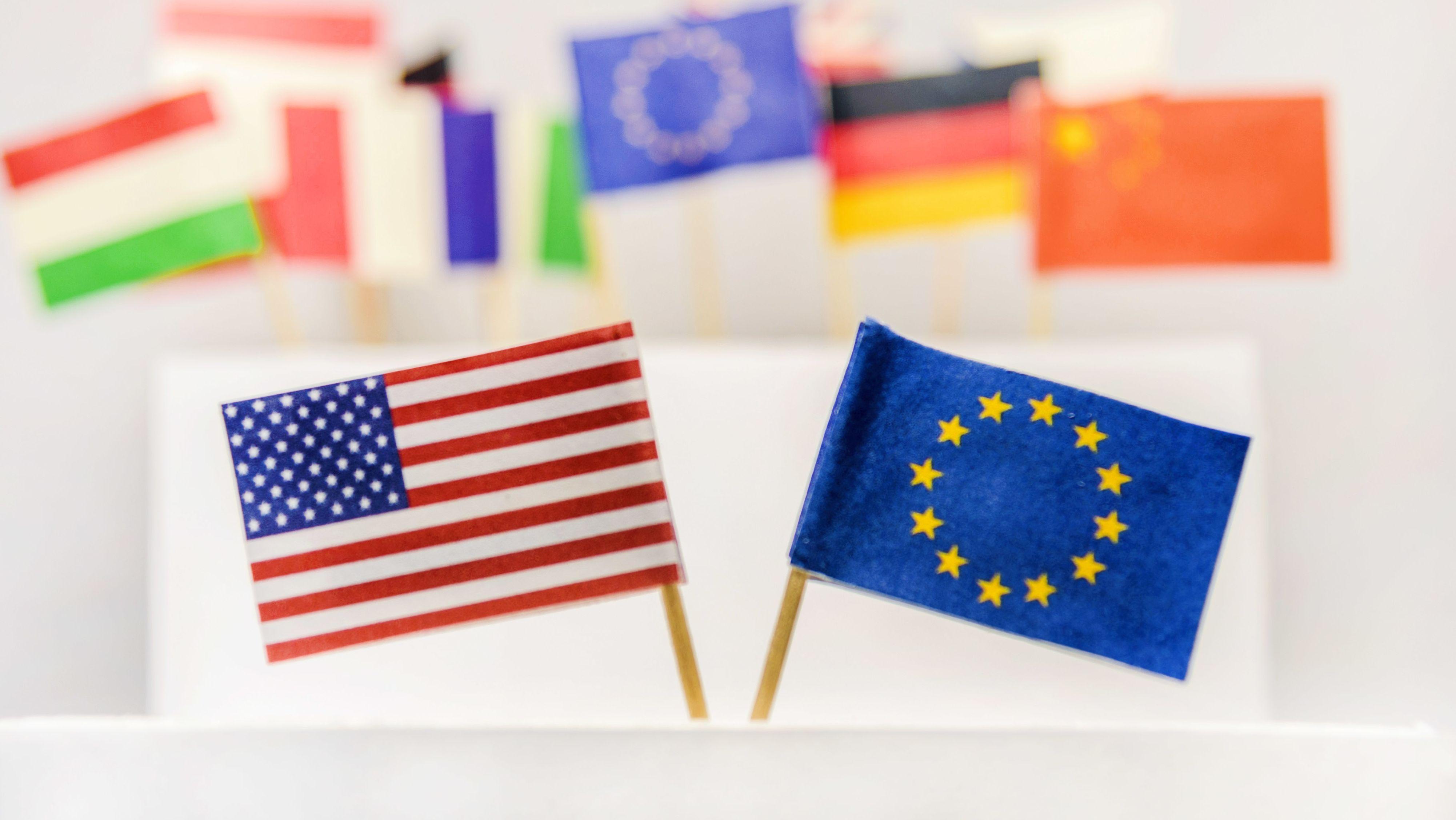 Im Vordergrund eine EU-Flagge und eine Flagge der USA, im Hintergrund mehrere europäische Flaggen