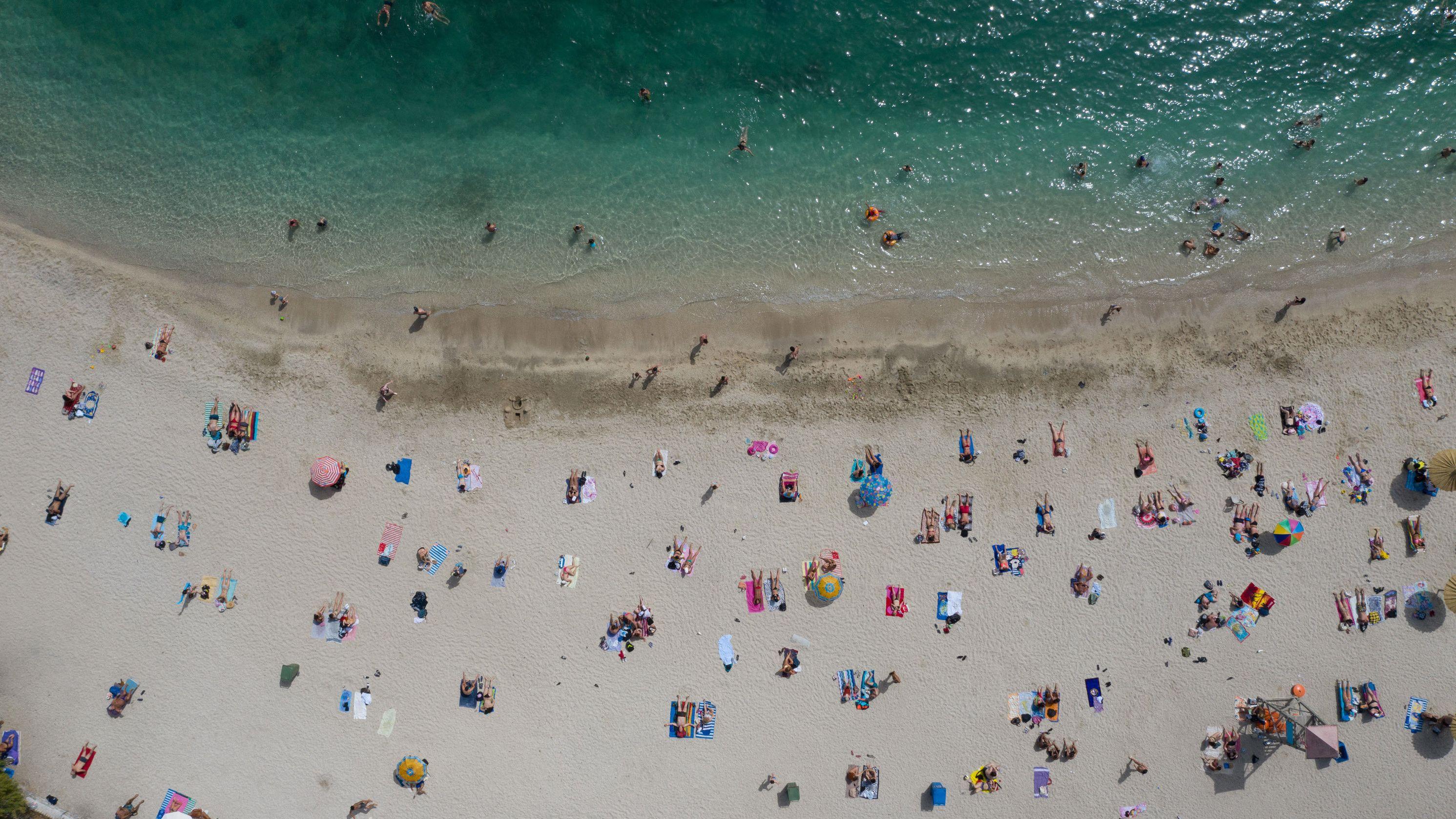 Besucher verbringen ihre Freizeit bei Sonnenschein am öffentlichen Strand von Alimos nahe Athen.
