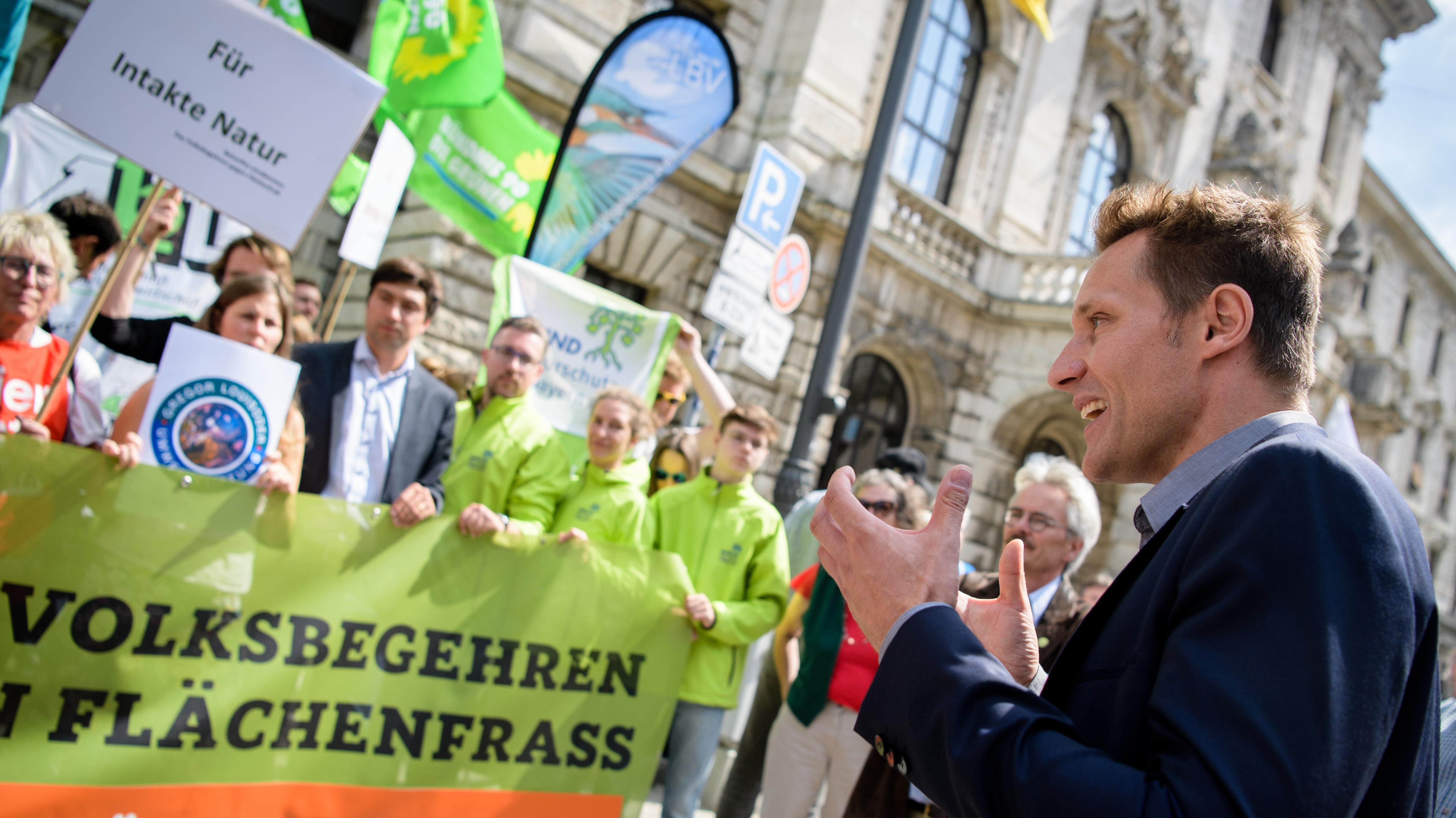 Ludwig Hartmann (r), Fraktionsvorsitzender von Bündnis 90/Die Grünen im Bayerischen Landtag, spricht vor den Unterstützern des Volksbegehrens gegen Flächenfraß in Bayern