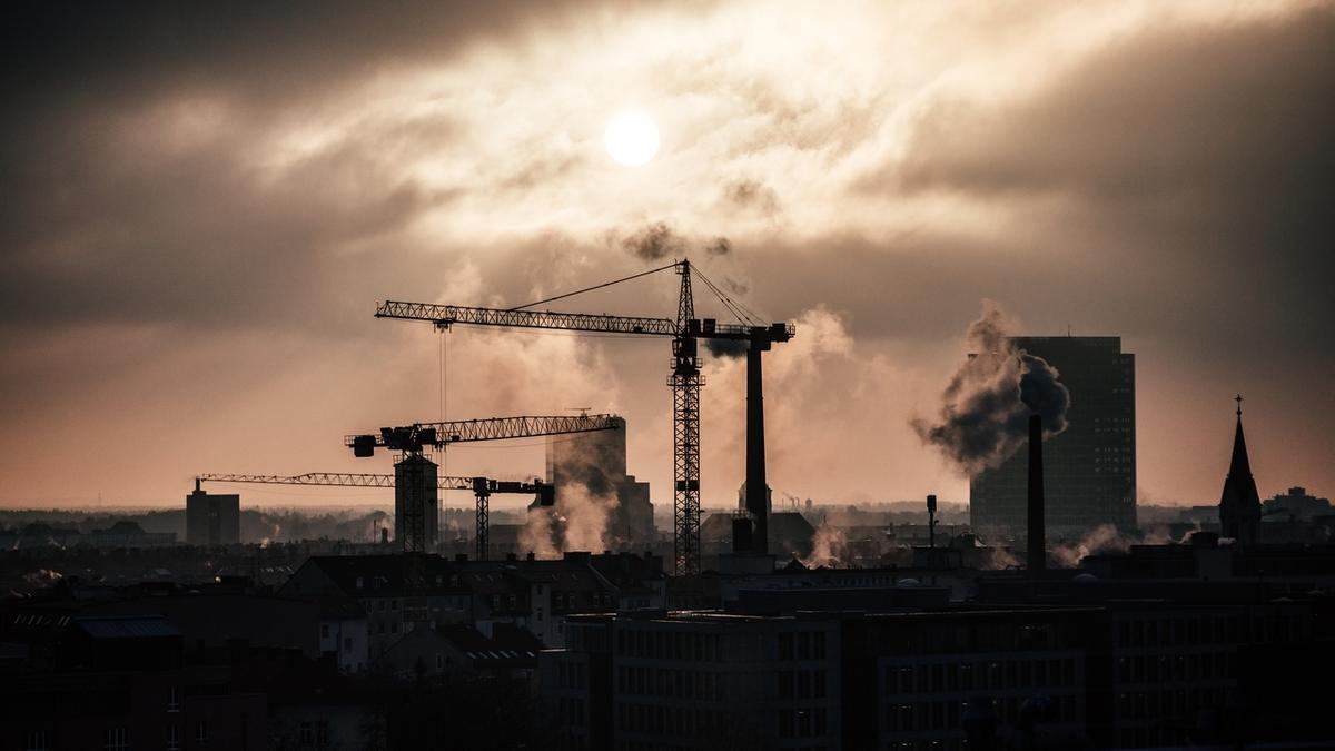 Baukräne und rauchende Schornsteine im Münchner Stadtteil Maxvorstadt bei Abendsonne. Das Klimaziel sieht vor, CO2-Emissionen zu senken.