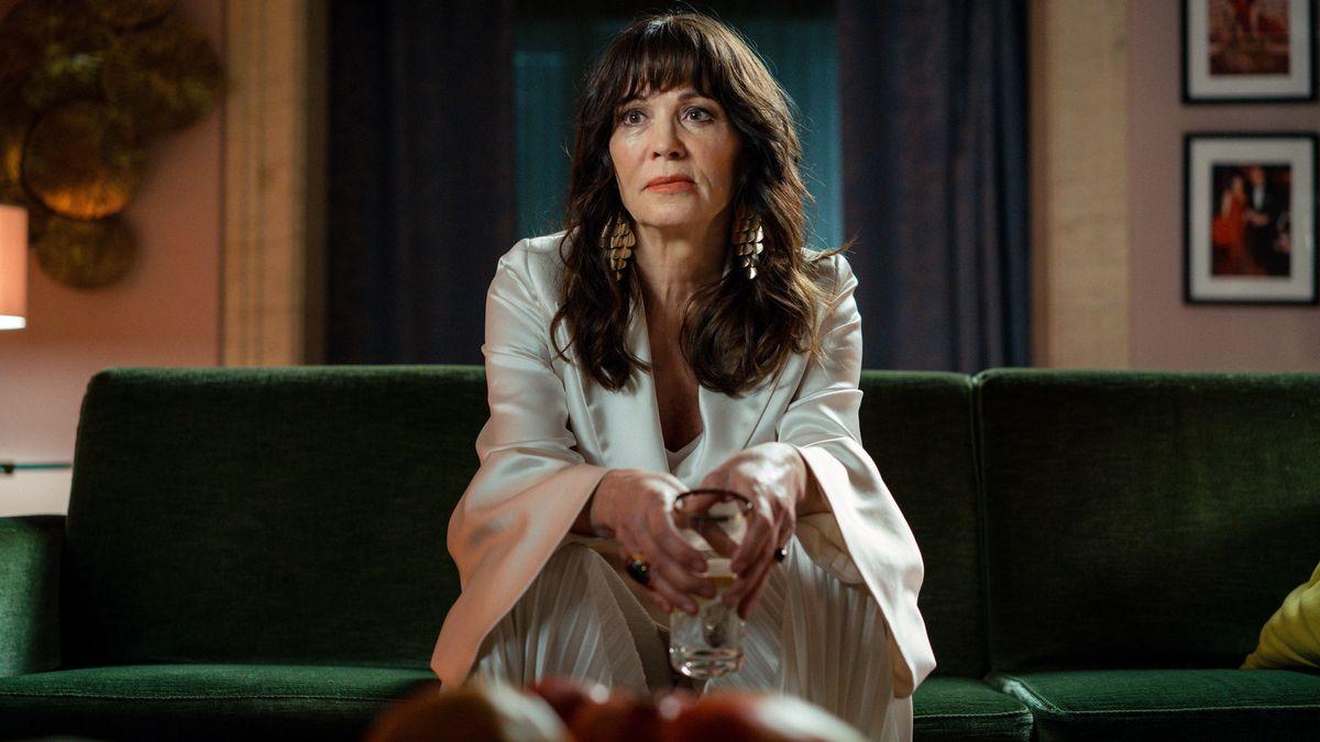 Eine ältere Frau mit langen dunklen Haaren und elegantem weißen Kostüm sitzt mit einem Glas auf einem grünen Sofa und schau desperat