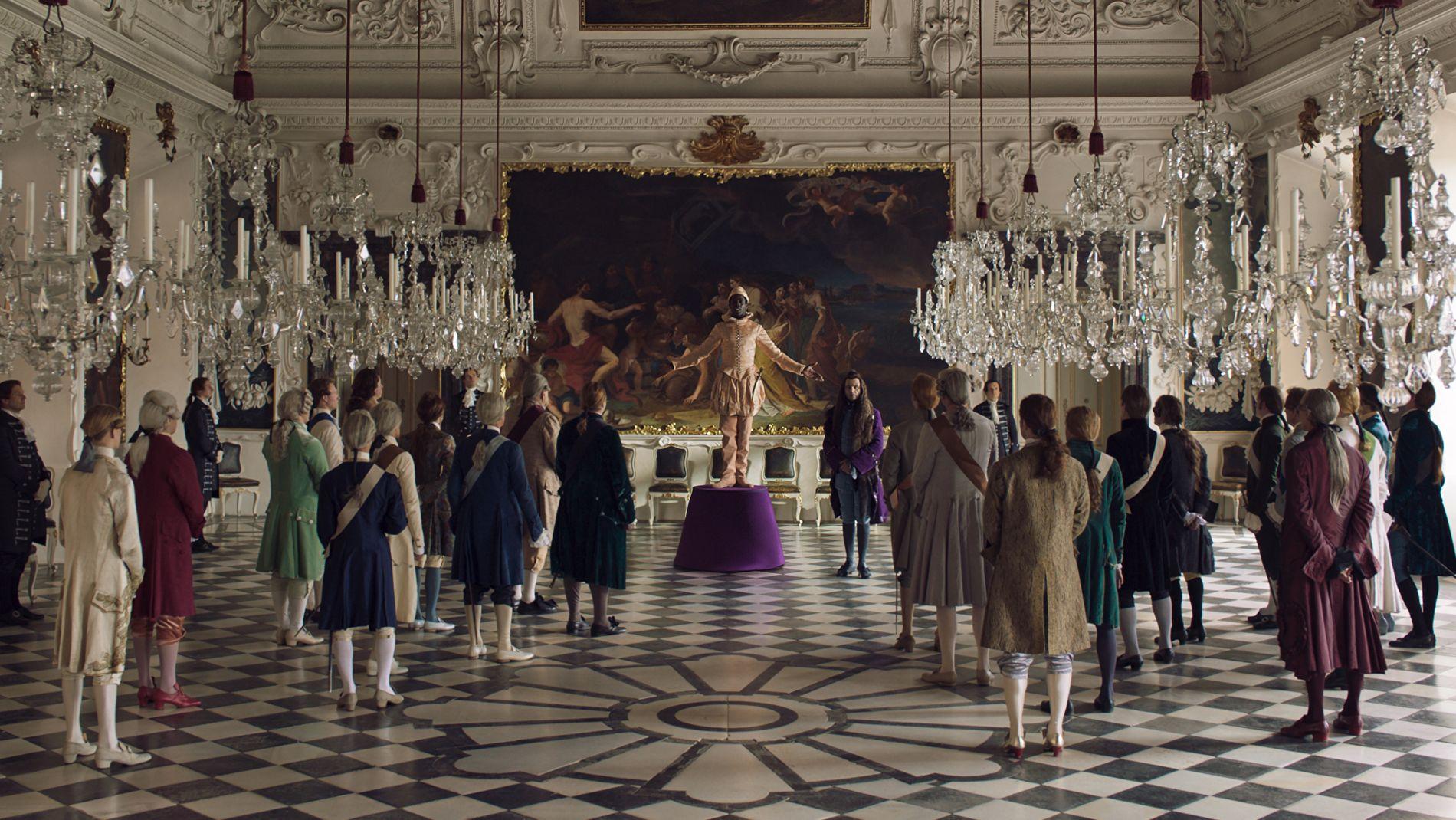 """In einem großen Saal betrachten einige Menschen einen Mann auf einem Podest. Es scheint als würde er ausgestellt werden. Szene aus """"Angelo"""""""
