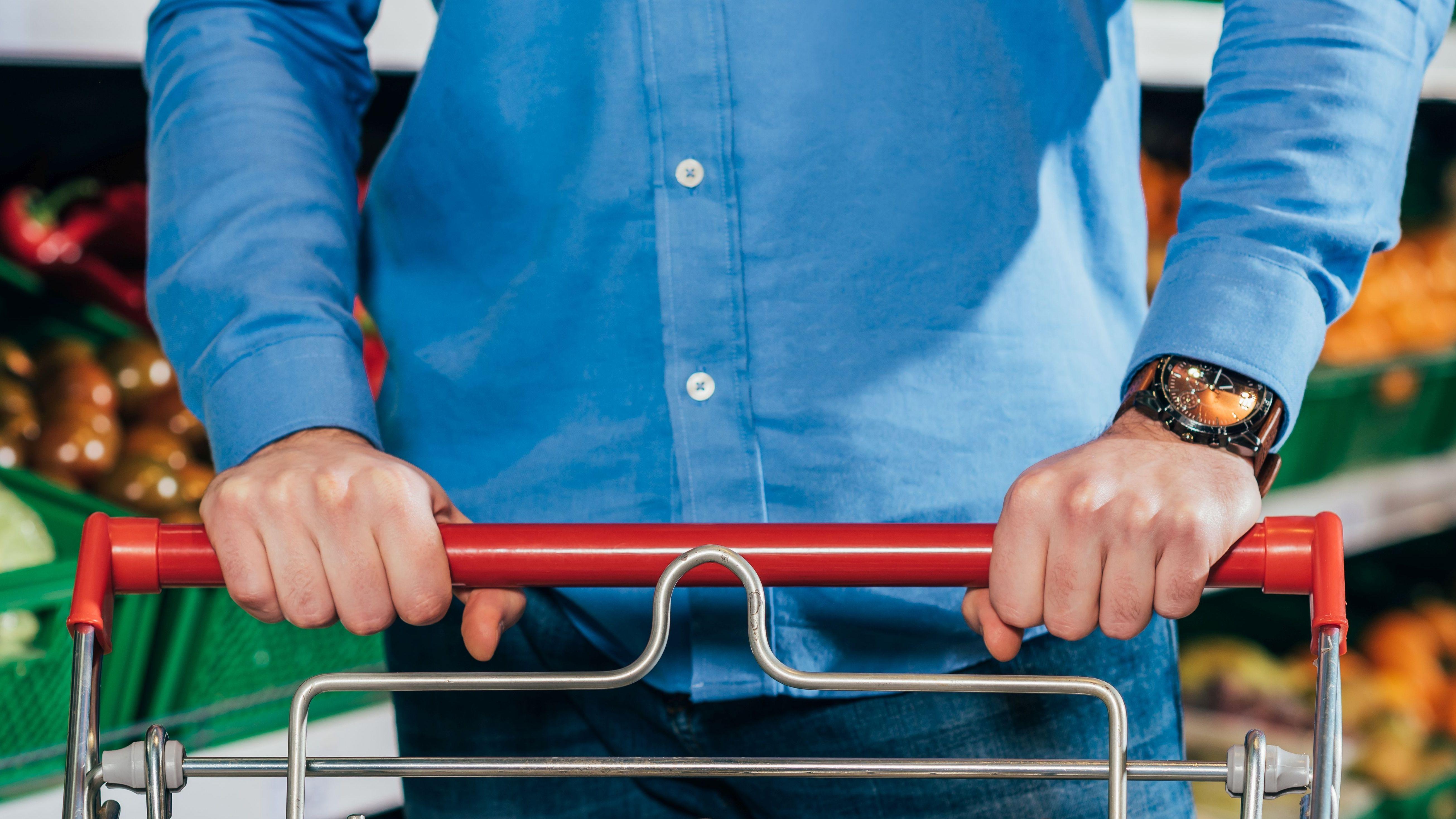 Mann mit Einnkaufswagen in Supermarkt
