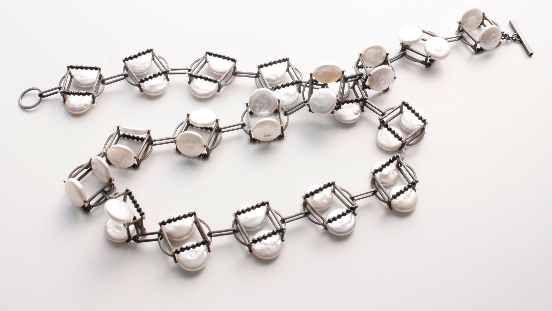Eine filigrane Halskette von Alexandra Bahlmann aus Eisen und kleinen Perlmutttalern