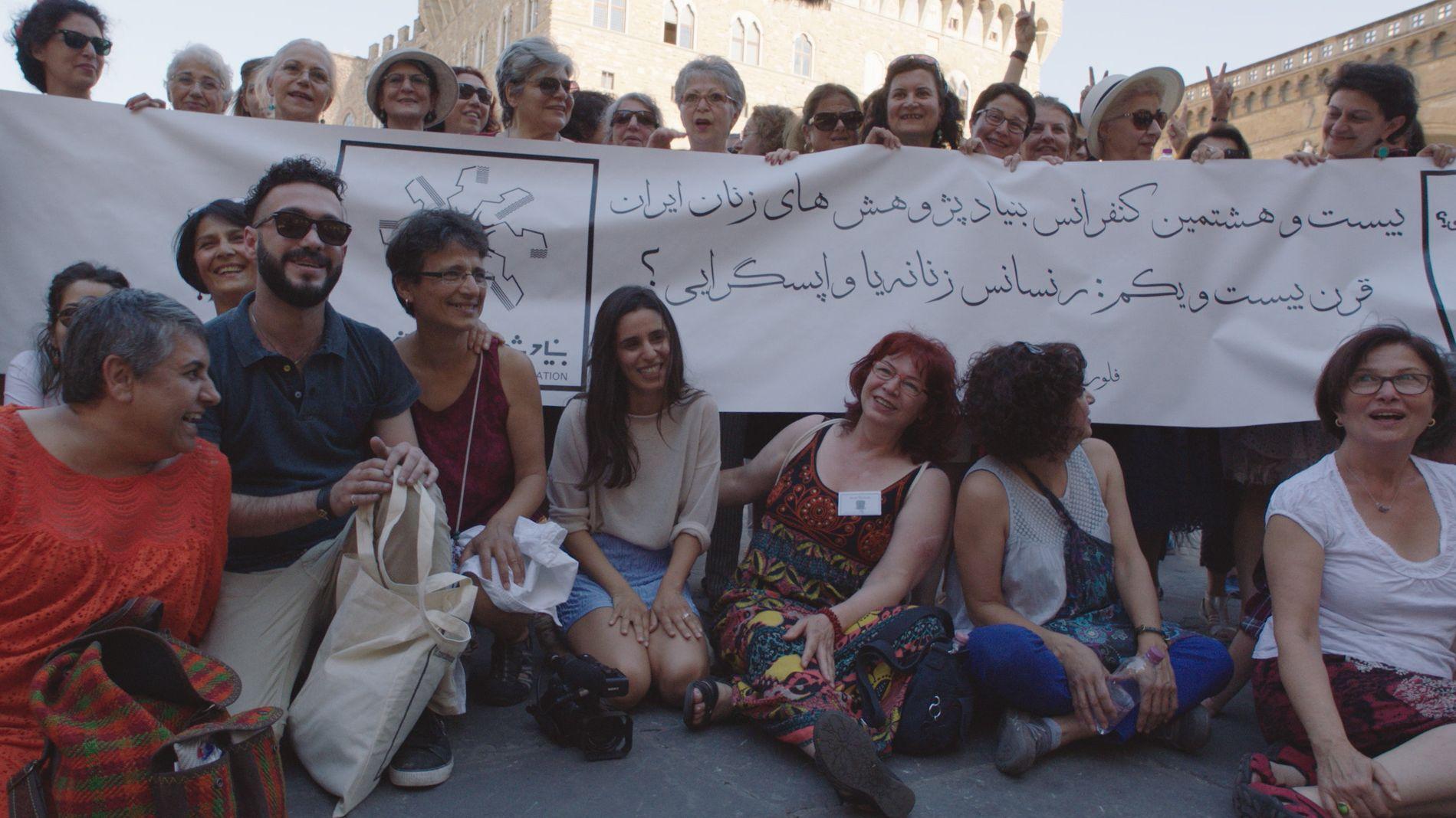 Maryam Zaree protestiert mit Exil-Iranern in Florenz, einige halten ein Banner in die Höhe