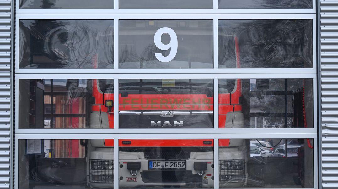 Ein Feuerwehrfahrzeug steht in der Gerätehalle der Feuerwache Offenbach hinter einem Rolltor.