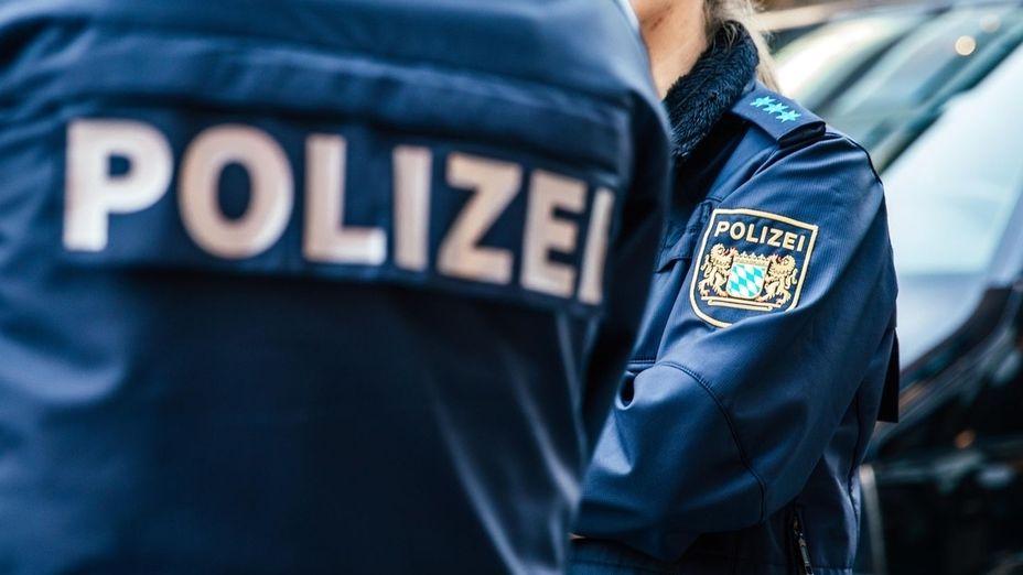 """Zwei Polizisten in blauer Uniform mit der Aufschrift """"Polizei"""" und dem Wappen von Bayern mit Löwen und weiß-blauen Rauten."""