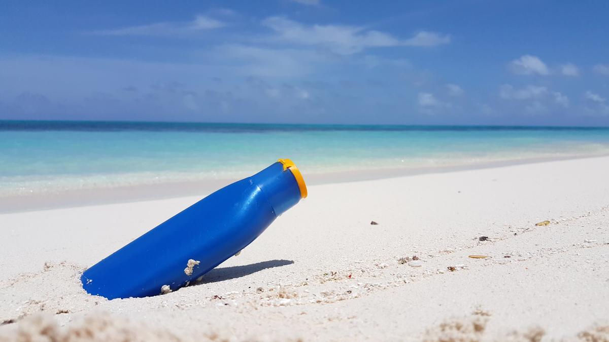 Eine Tube mit Sonnencreme steckt im Sand, dahinter das Meer.
