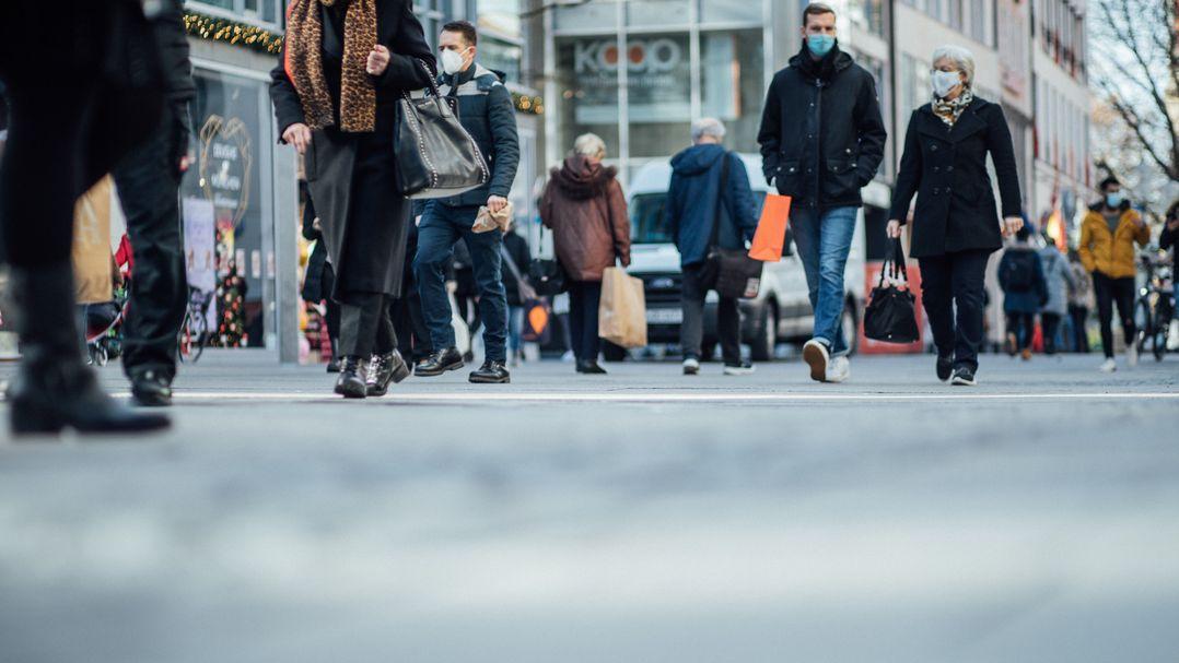 Fußgänger flanieren mit Masken in der Innenstadt