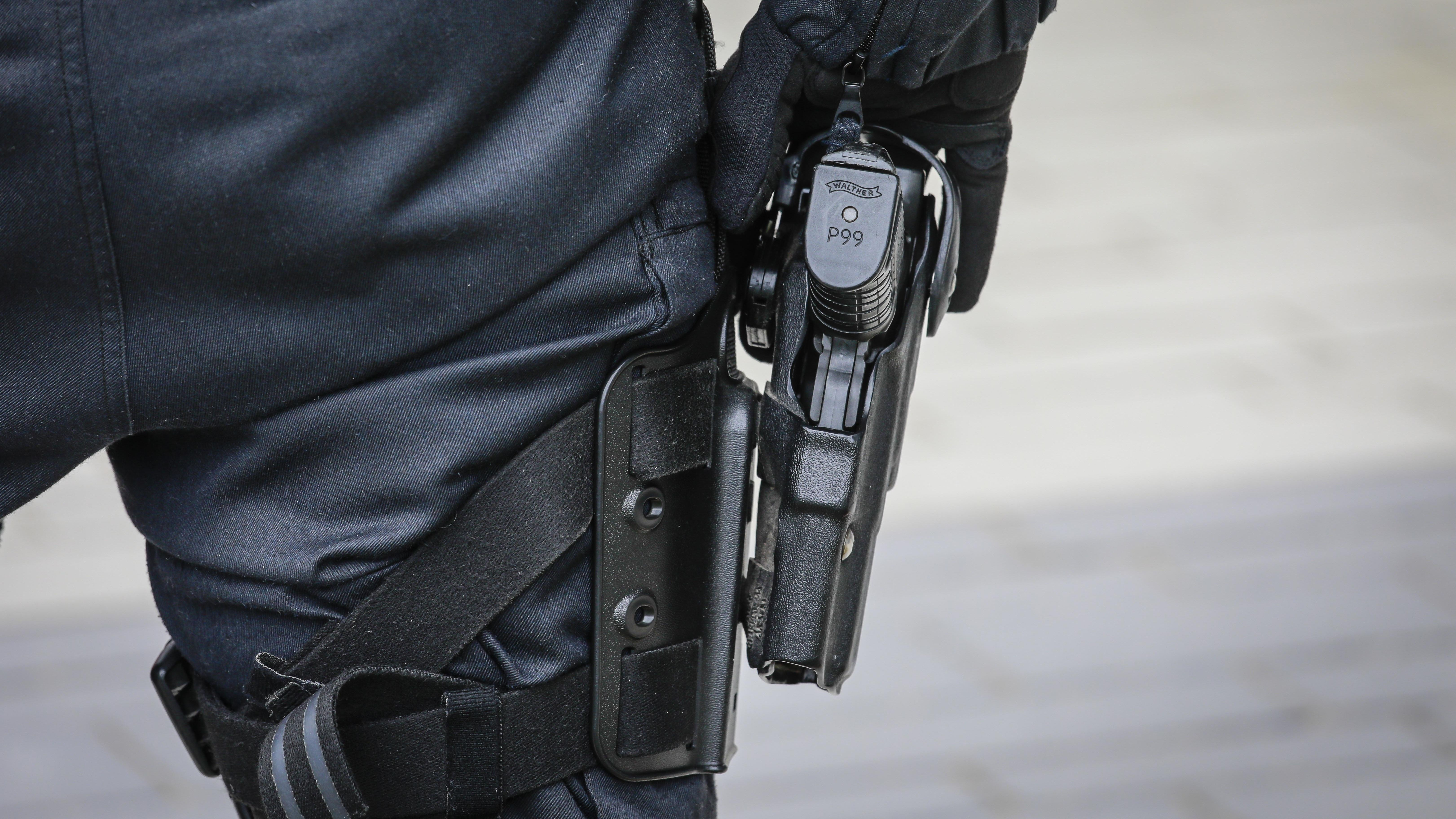 Ein Polizist im Einsatz greift an seine Dienstwaffe