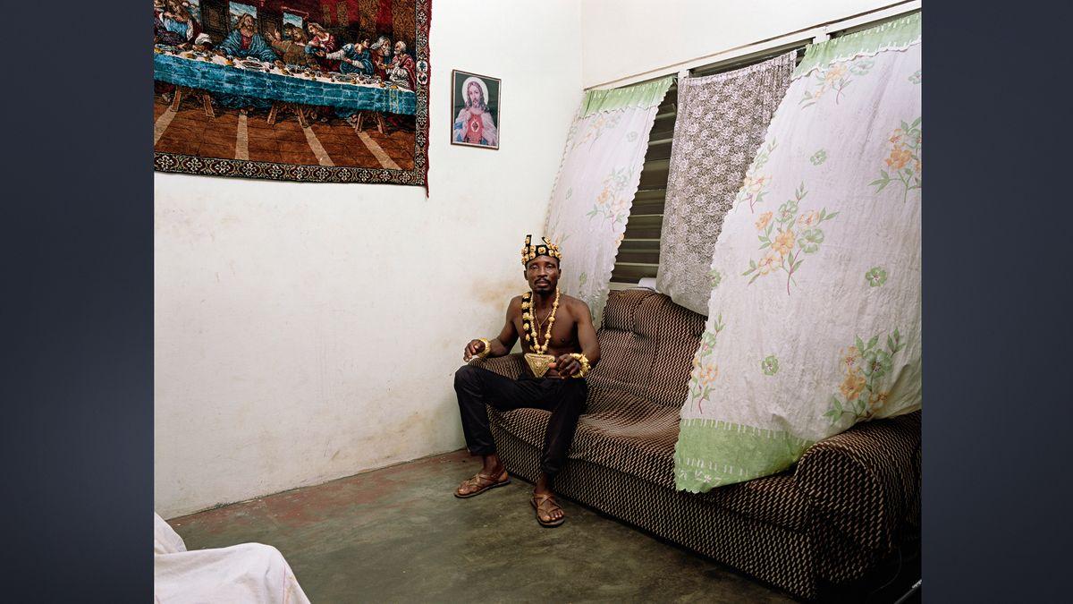 """Fotografie """"Chief"""" (2019): Schwarzer Mann sitzt mit nacktem Oberkörper, Kopfschmuck und Halskette auf einem Sofa unter einem von Gardinen und Rollos abgeschirmten Fenster"""