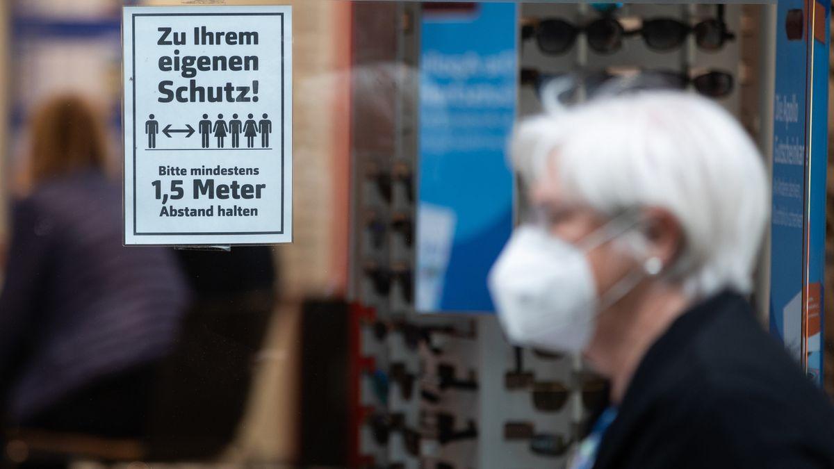 """Eine Frau mit Mundschutz geht an einem Schild mit der Aufschrift """"Zu Ihrem eigenen Schutz! Bitte mindestens 1,5 Meter Abstand halten"""" vorbei."""