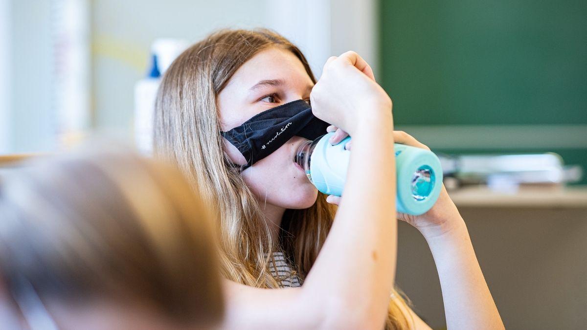 Eine Schülerin der Klasse 8a der Gesamtschule in Münster, hebt ihre Mund- und Nasenmaske an um etwas zu trinken. Das Bundesland Nordrhein-Westfalen startet mit Maskenpflicht nach den Sommerferien wieder in den Regel-Schulbetrieb.
