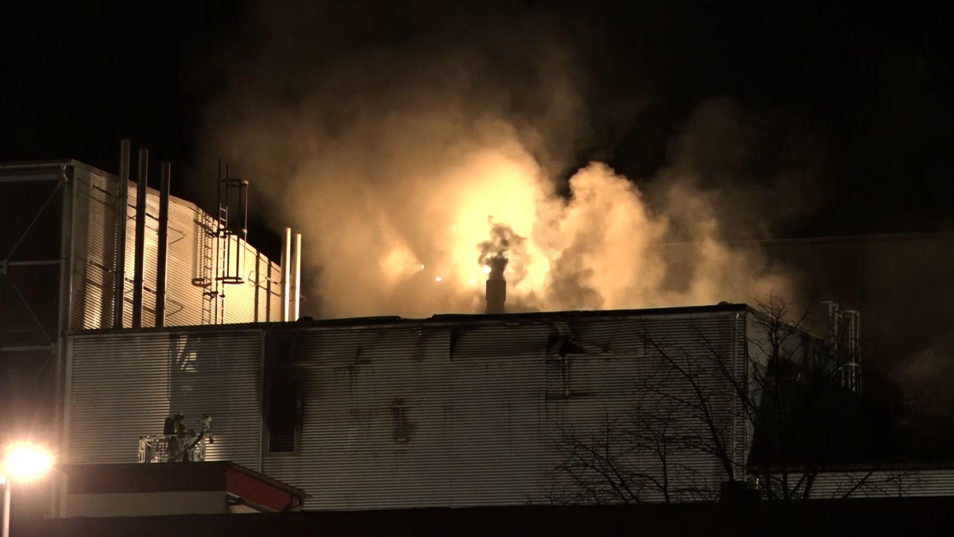 Rauchwolken steigen über einem Firmengebäude auf.