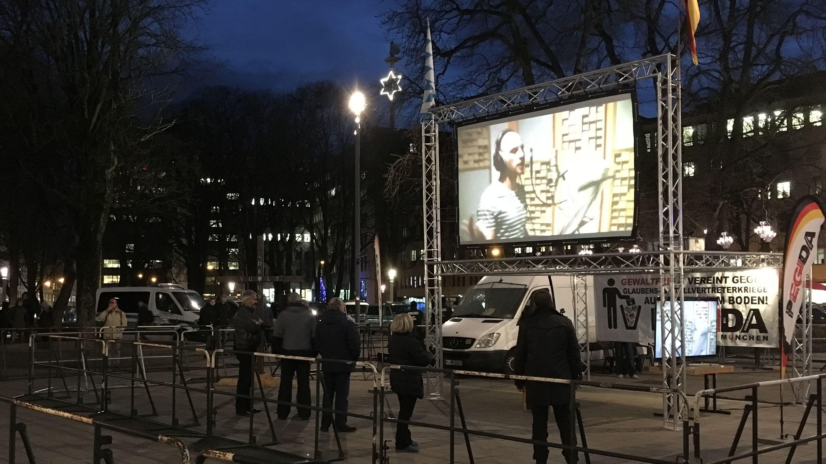 Nur fünf Personen stehen neben einem Pegida-Plakat am Königsplatz in Augsburg