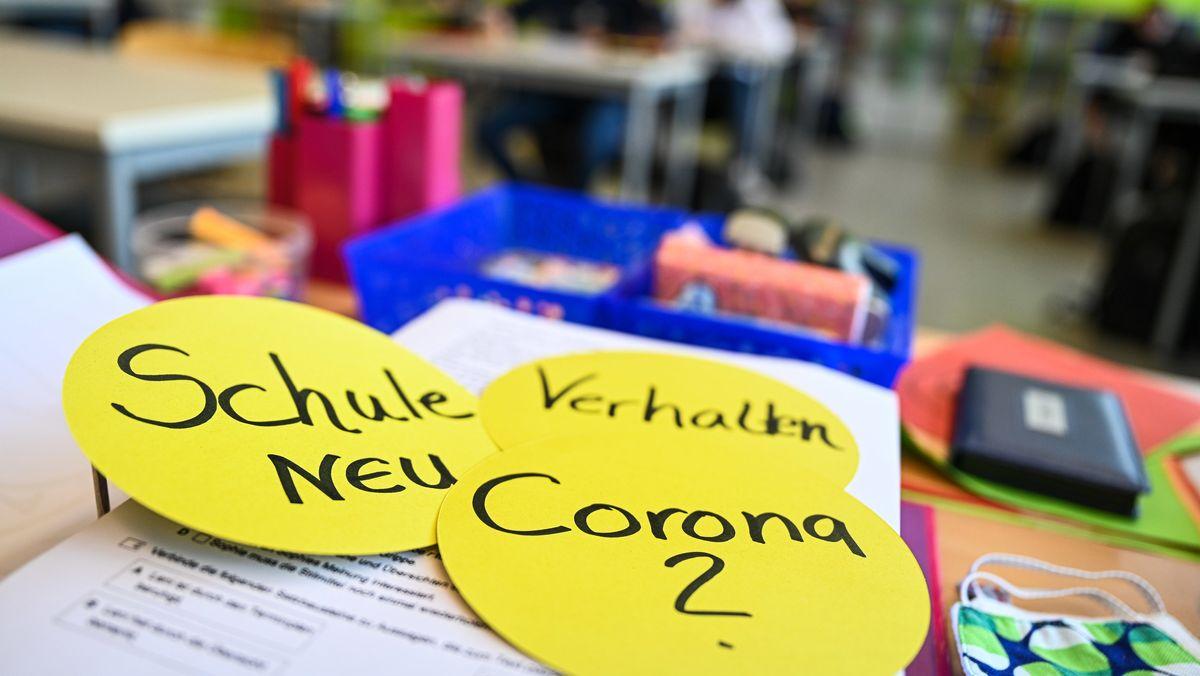 """Aufnahme aus einem Klassenzimmer in Baden-Württemberg mit Unterlagen und Papierschildern auf dem Tisch. Aufschrift auf den Schildern: """"Corona?"""", """"Schule NEU"""" und """"Verhalten""""."""