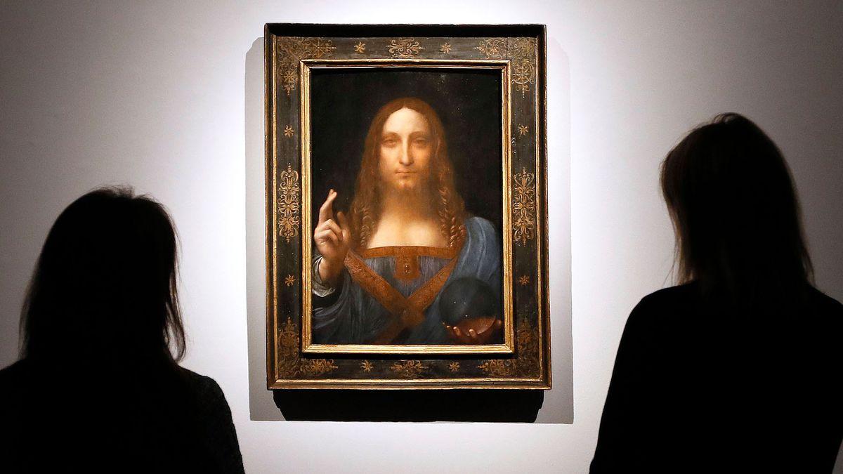 """Das Gemälde """"Salvator Mundi"""" flankiert von Besucherinnen im Schatten."""