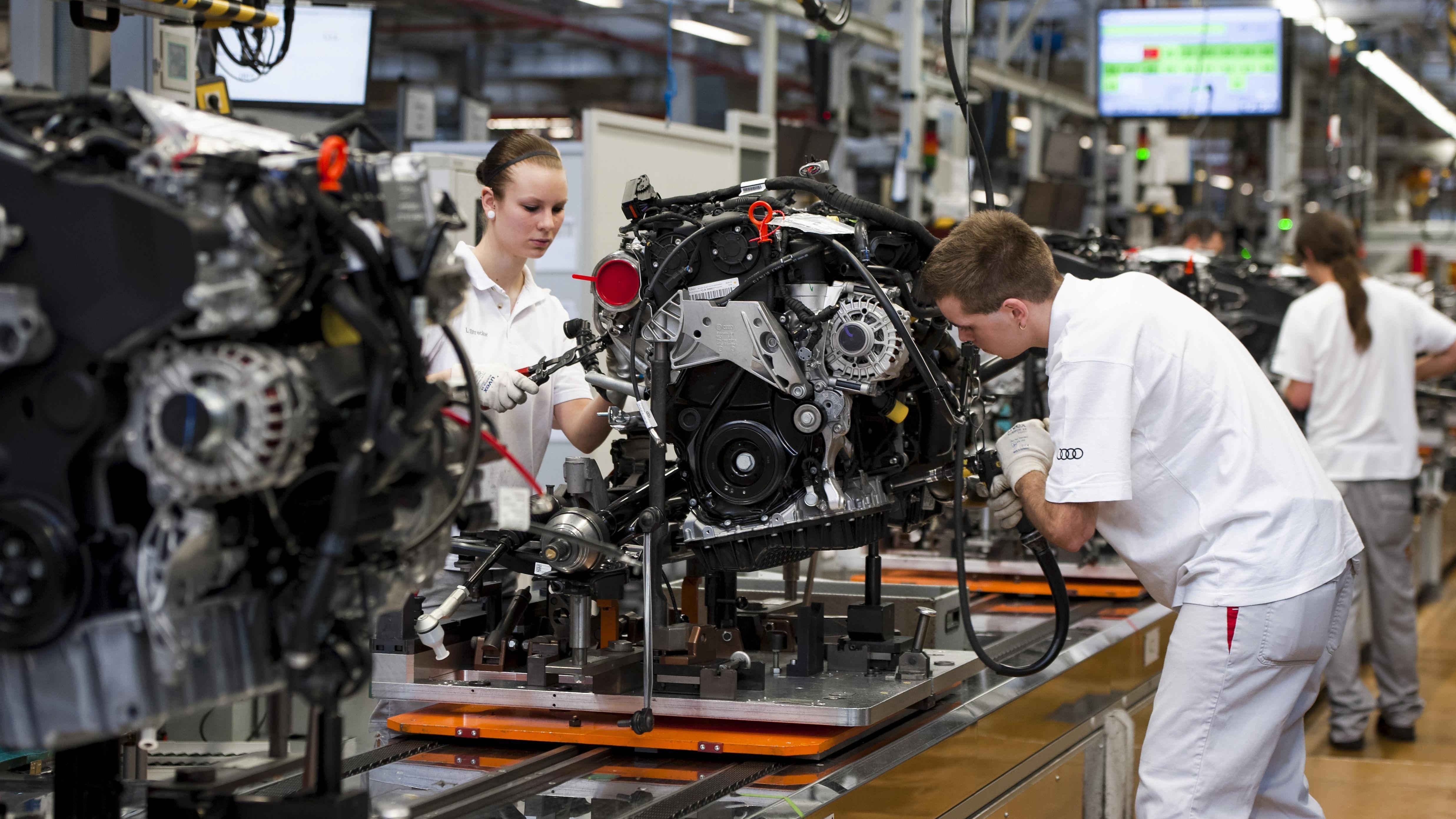 Eine Frau und ein Mann arbeiten an der Fertigungslinie für den Audi A3 im Audi Werk in Ingolstadt.