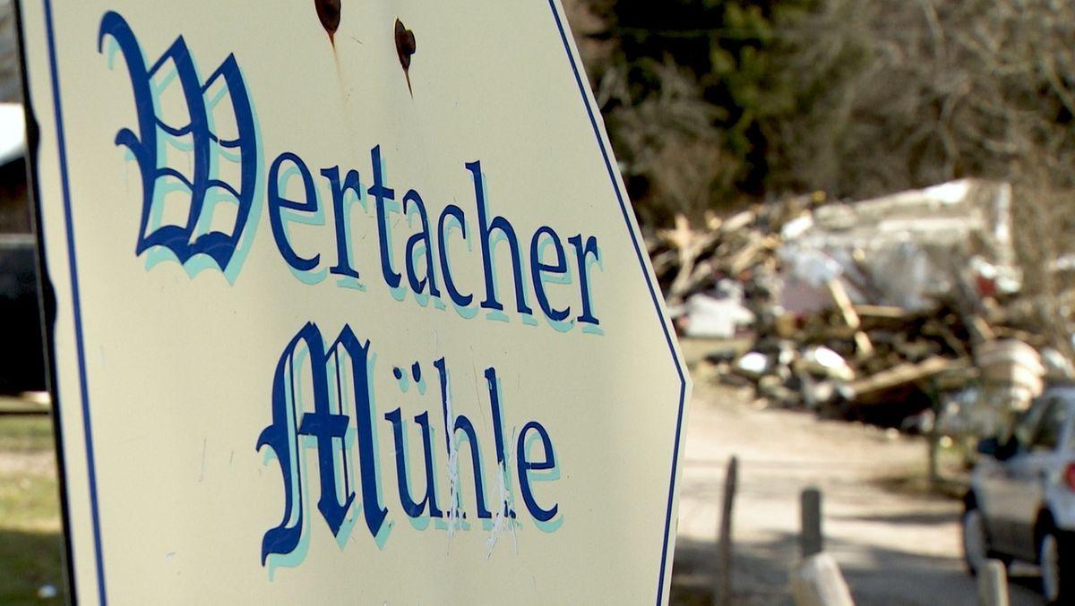 Schild Wertacher Mühle mit Trümmern im Hintergrund