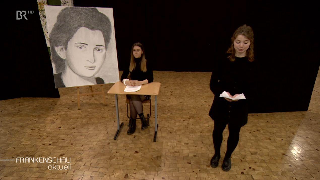 In schwarz gekleidete Schülerinnen stehen vor großen Porträts jüdischer Frauen.