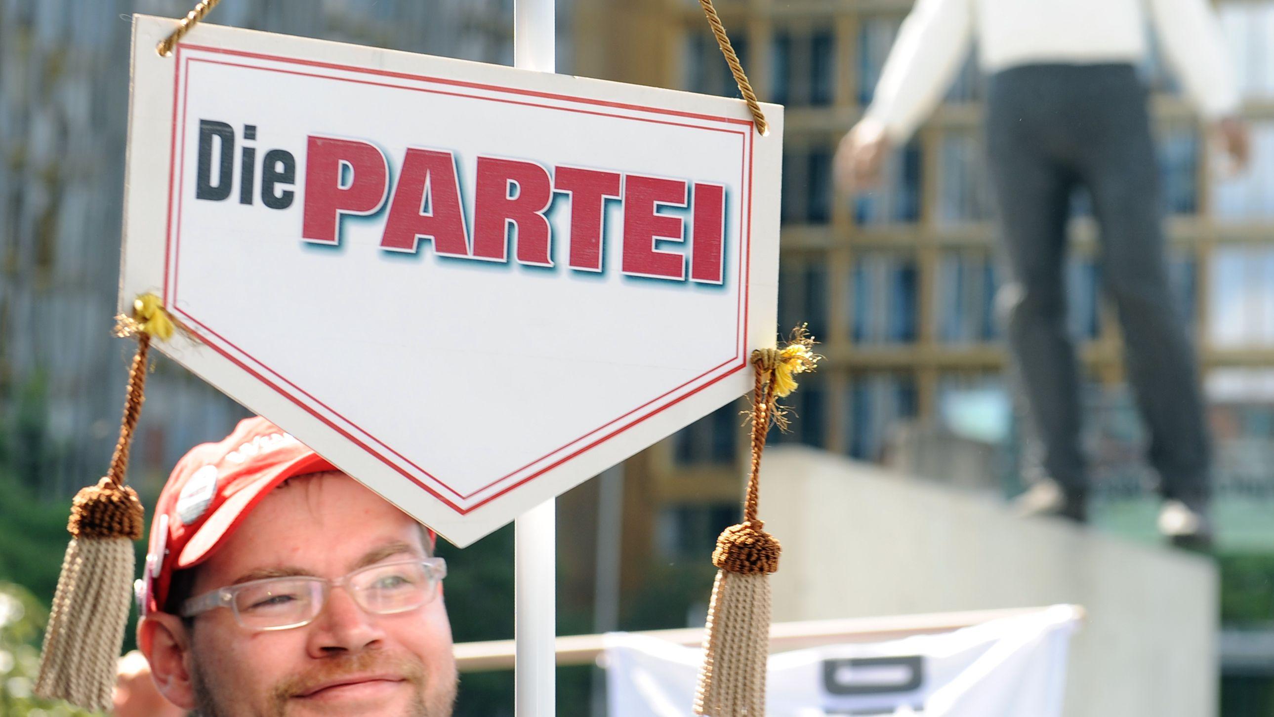 """Bei einer satirischen Aktion hält ein Mitglied der """"Partei"""" einen Wimpel in die Luft."""