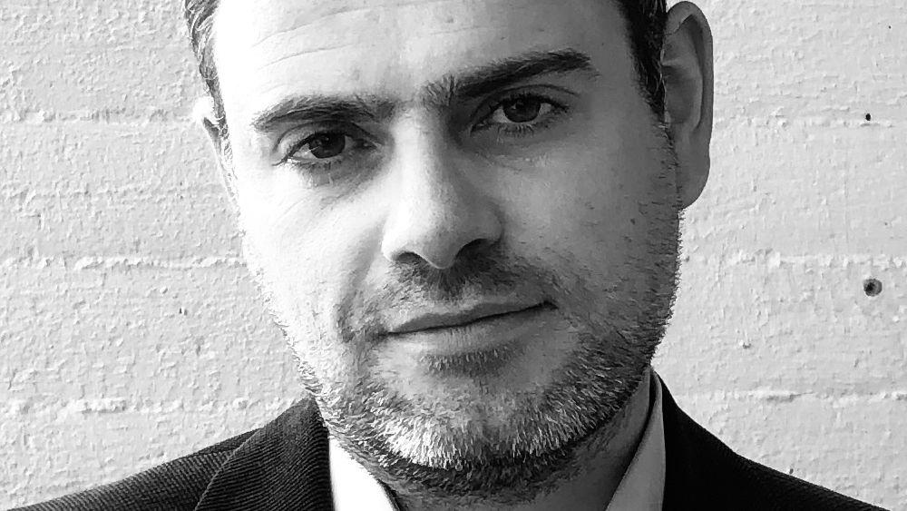 Schwarzweiß-Foto eines Mannes im Anzug mit grau meliertem, kurzen Bart