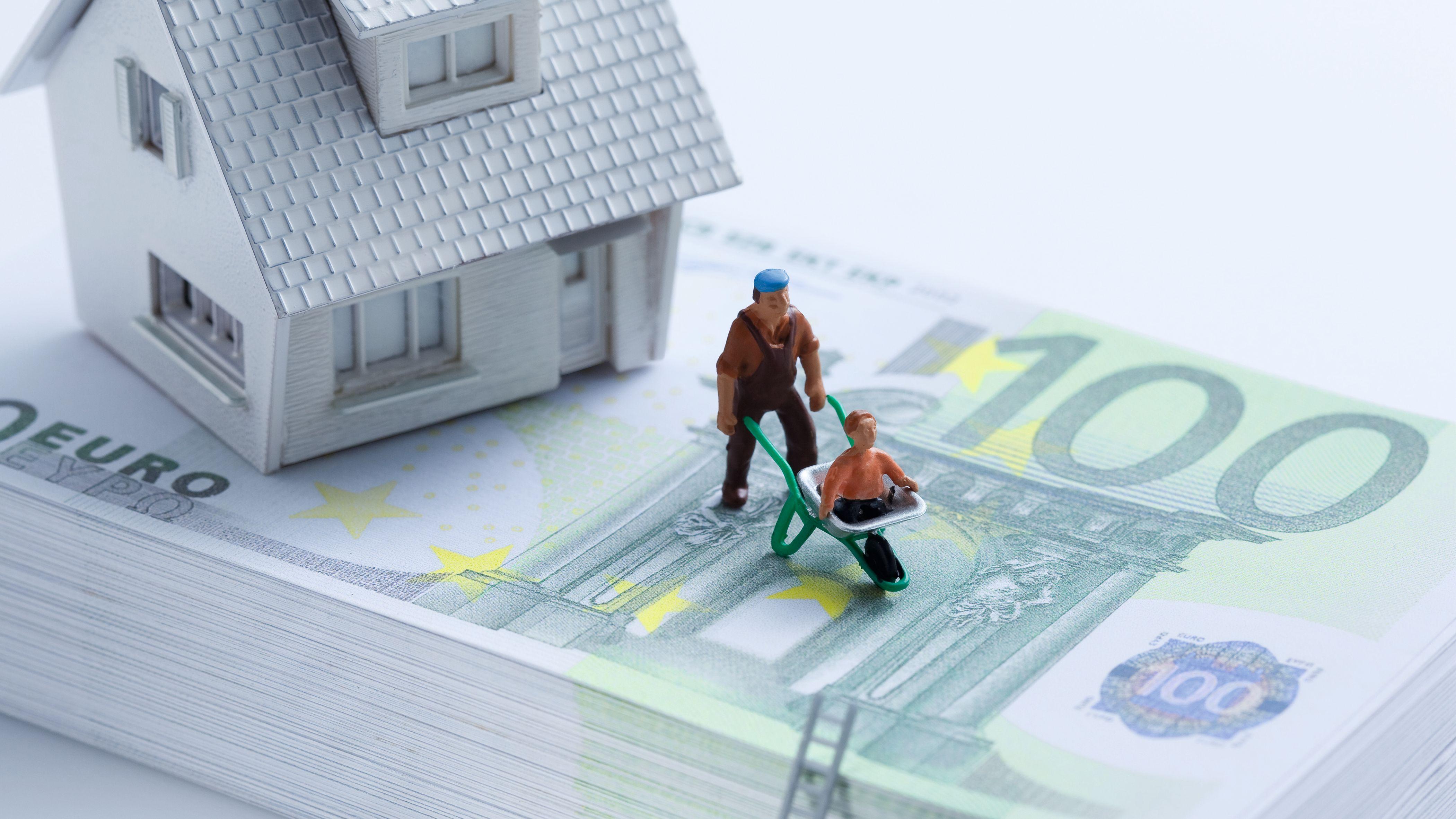 Haus und Spielfiguren auf Geldbündel (Symbolbild).