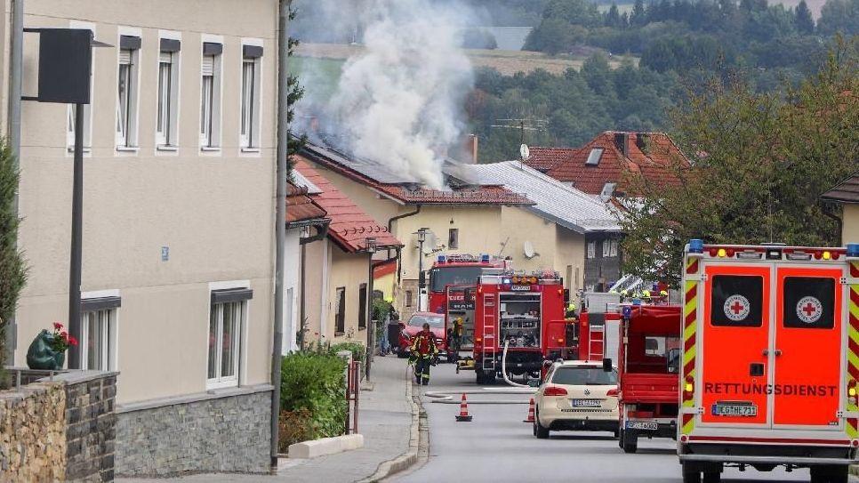 Die Straße voller Einsatzfahrzeuge vor dem brennenden Haus
