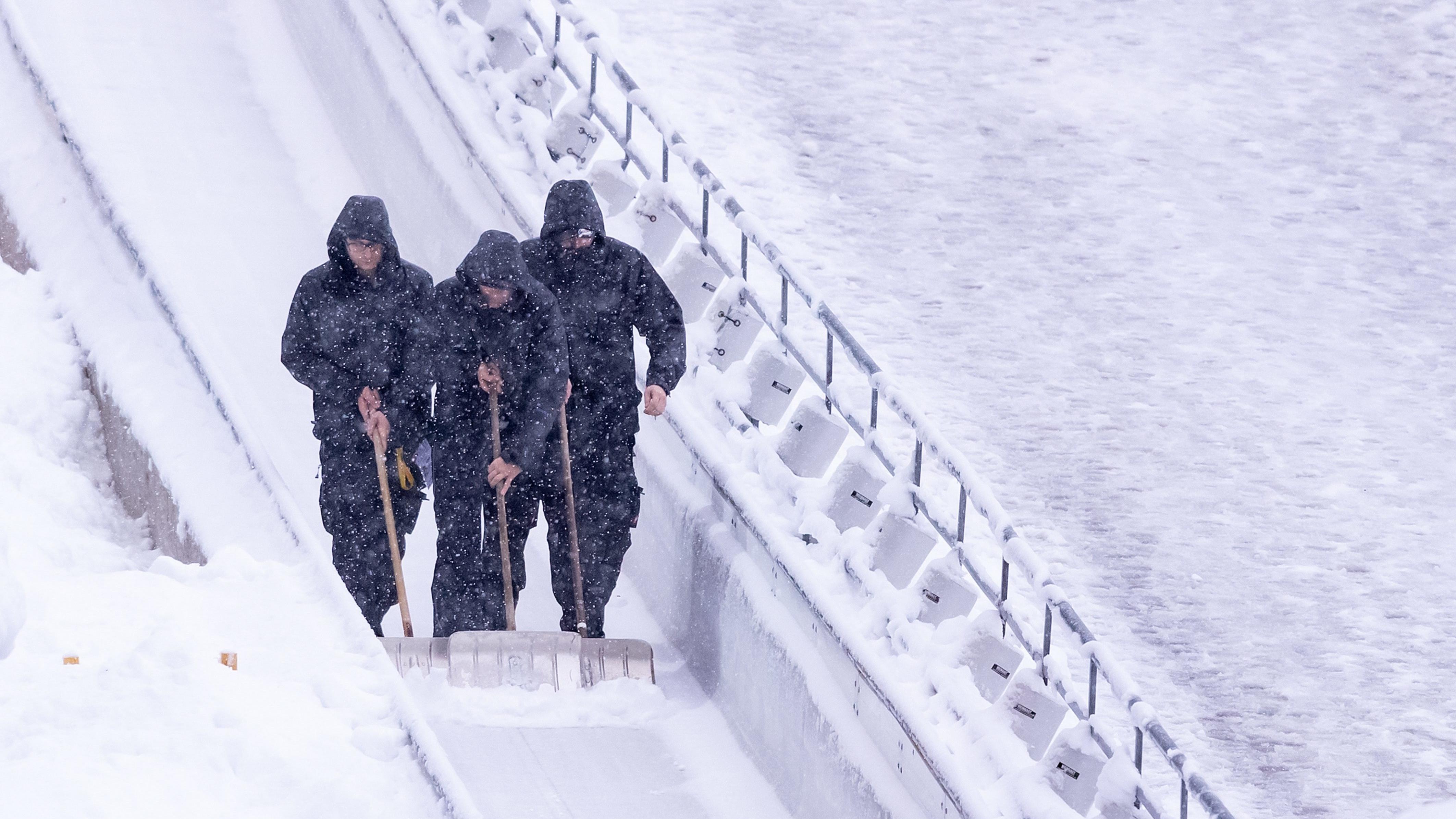 Männer mit Schneeschaufeln auf der Rodelbahn am Königssee