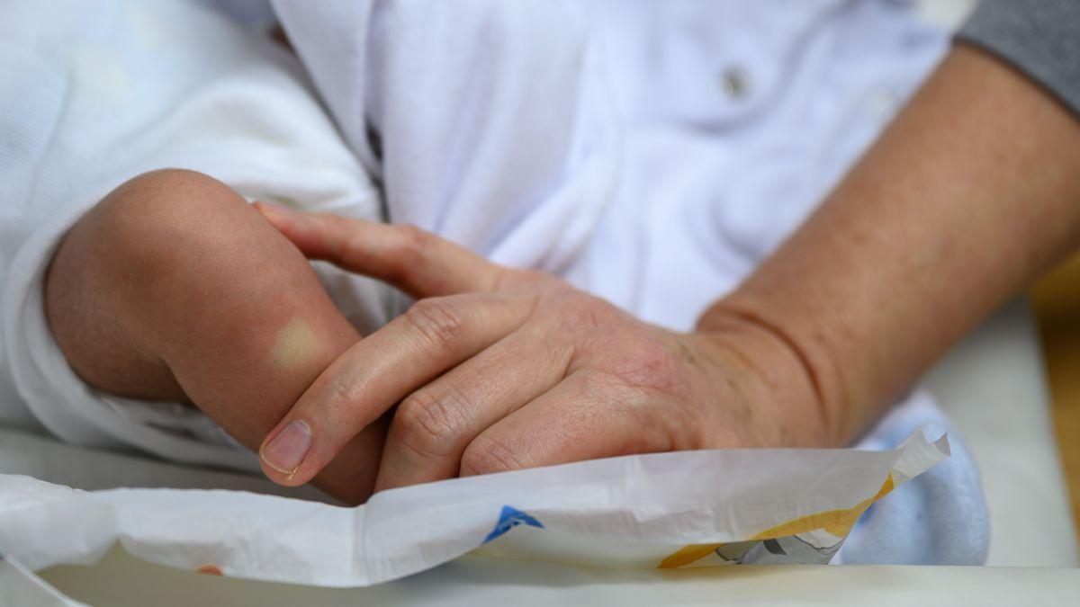 Ein Erwachsener streichelt das Bein eines Neugeborenen. (Symbolbild)