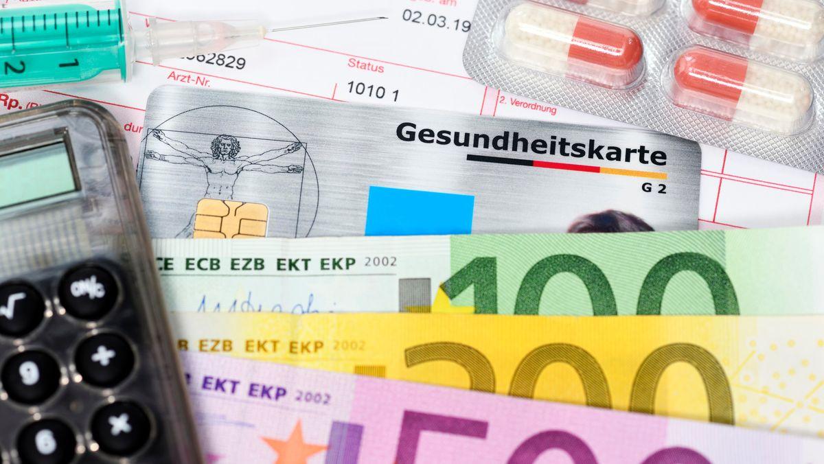 Geldscheine, Medikamente, eine Gesundheitskarte, ein Taschenrechner und eine Spritze liegen auf einem Schreibtisch (Symbolbild)