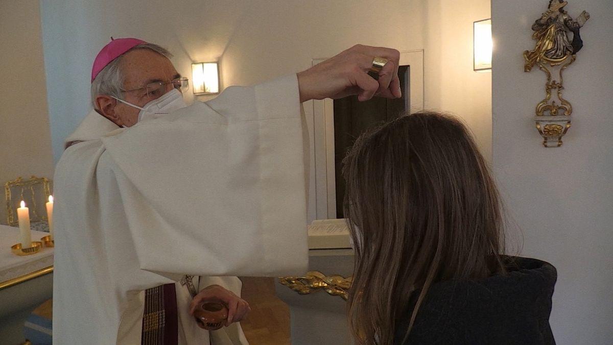 Der Bamberger Erzbischof Ludwig Schick mit Mundschutz spendete einer Frau das Aschenkreuz.