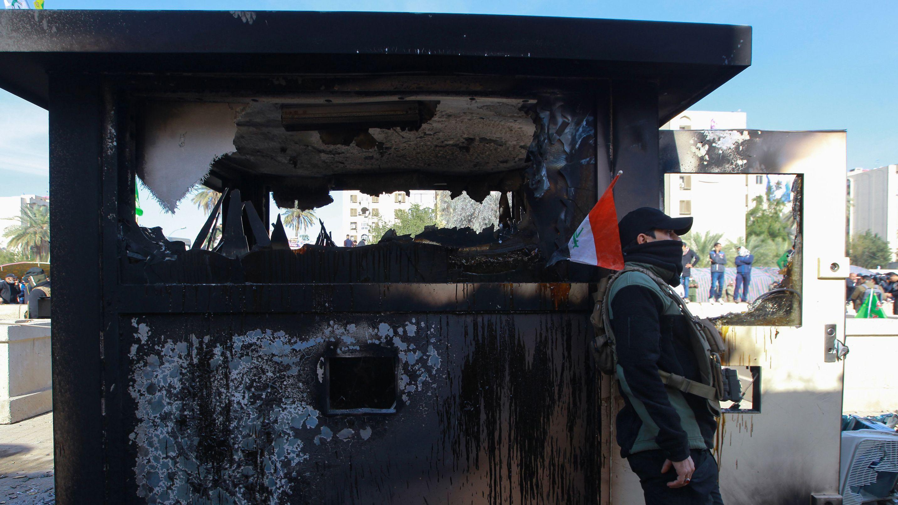 Ein Protestler steht vor einem abgebrannten Wachhäuschen auf dem Gelände vor der US-Botschaft.