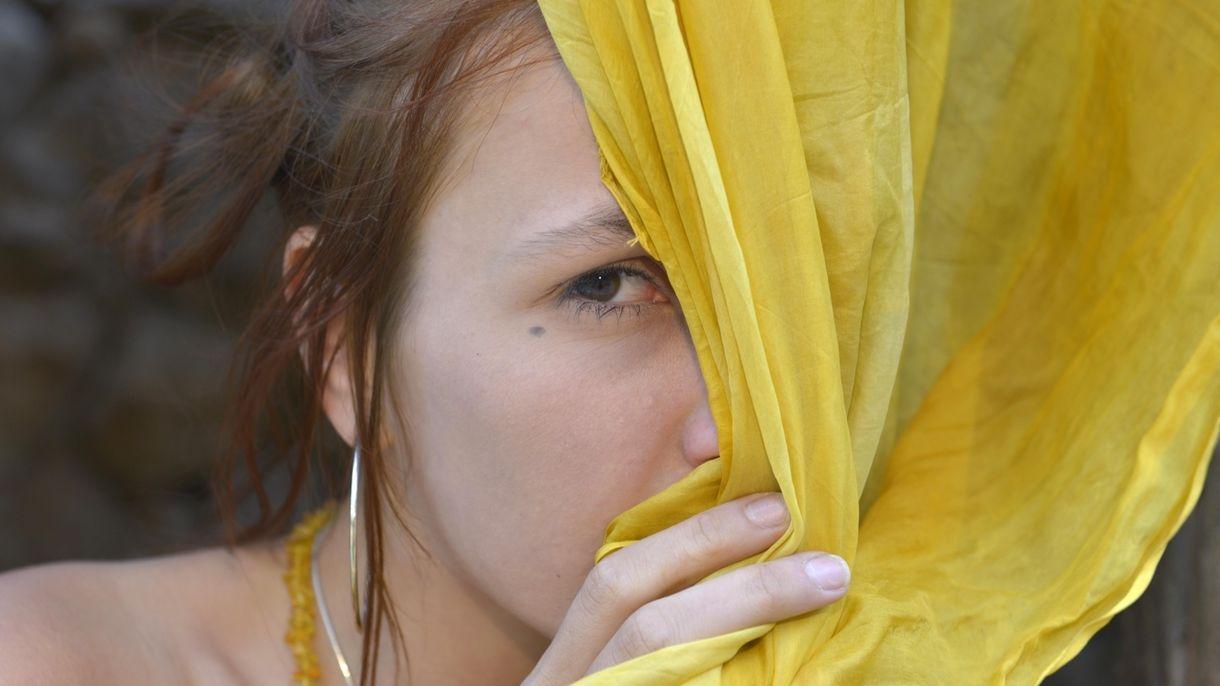 Junge Frau versteckt sich hinter einem Seidenschal.