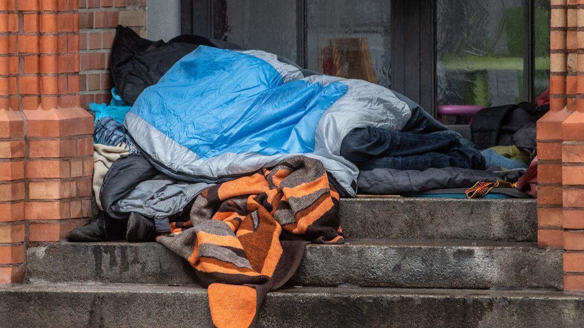 Ein Obdachloser liegt unter einer Decke in einem Hauseingang (Symbolbild)